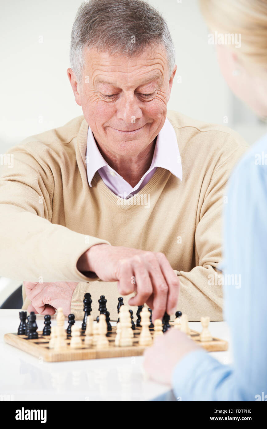 Senior Man Playing Chess With Teenage Granddaughter - Stock Image