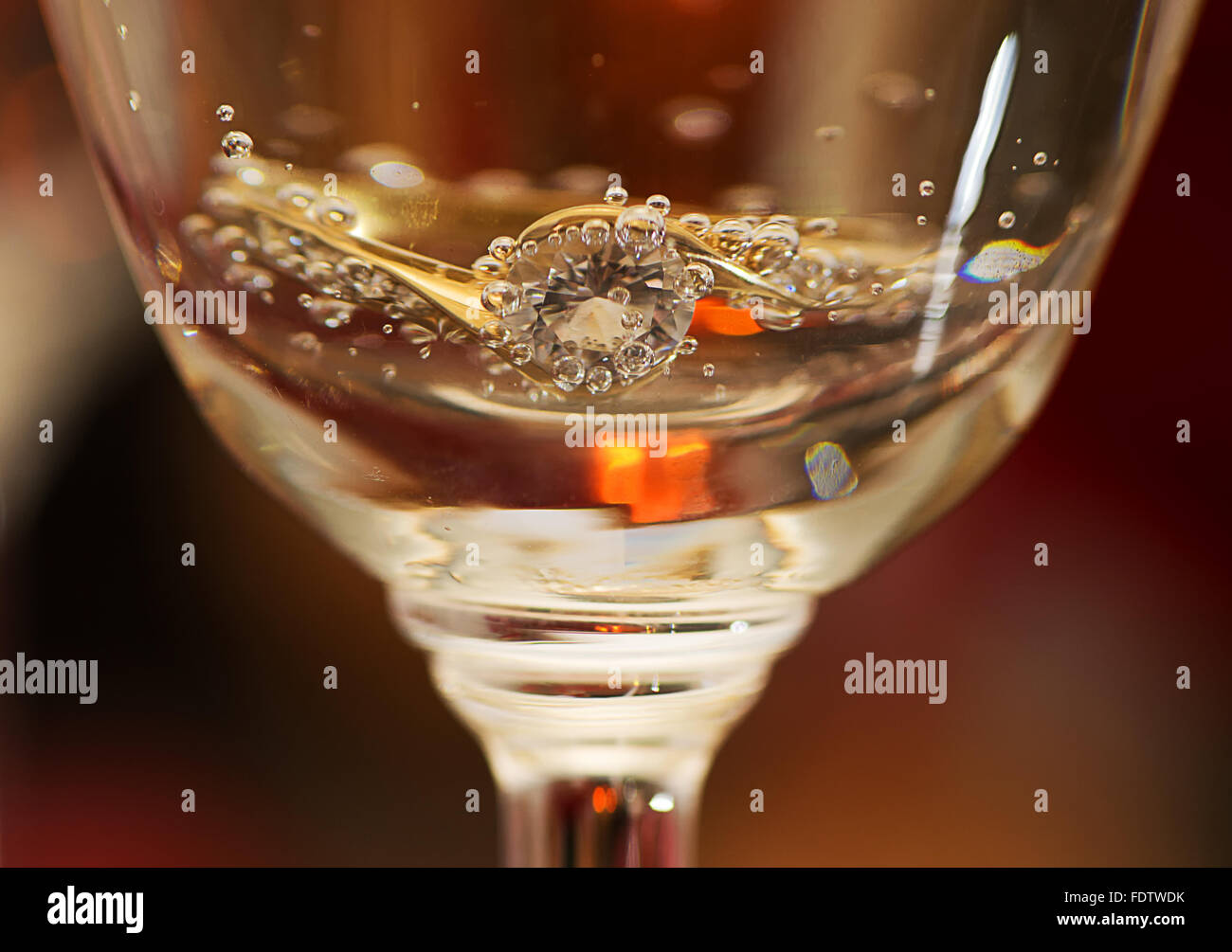 An engagement ring in a glass of champagne. - Stock Image