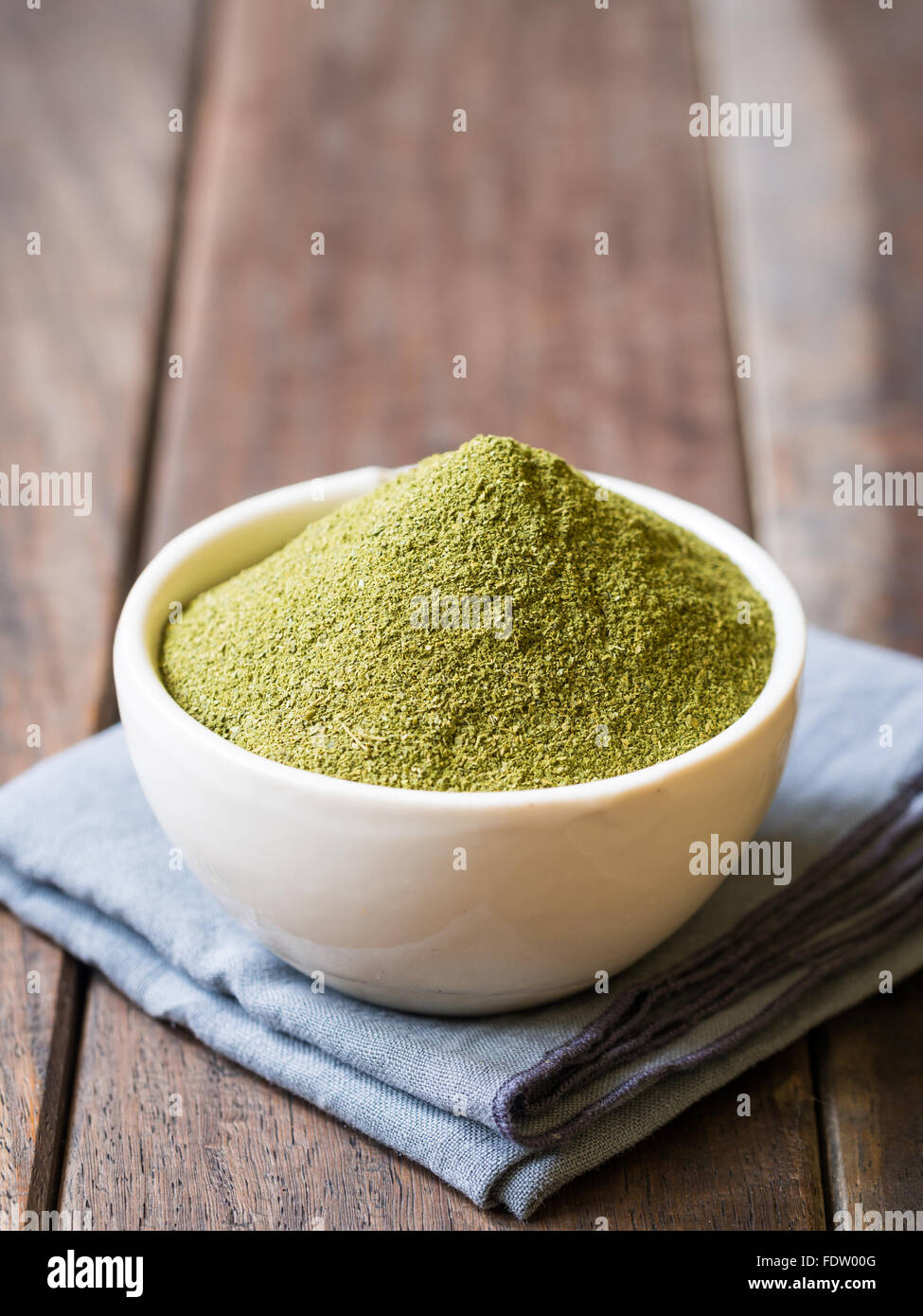 Moringa powder (superfood) in a white bowl on a wooden rustic background. Vertical orientation. - Stock Image
