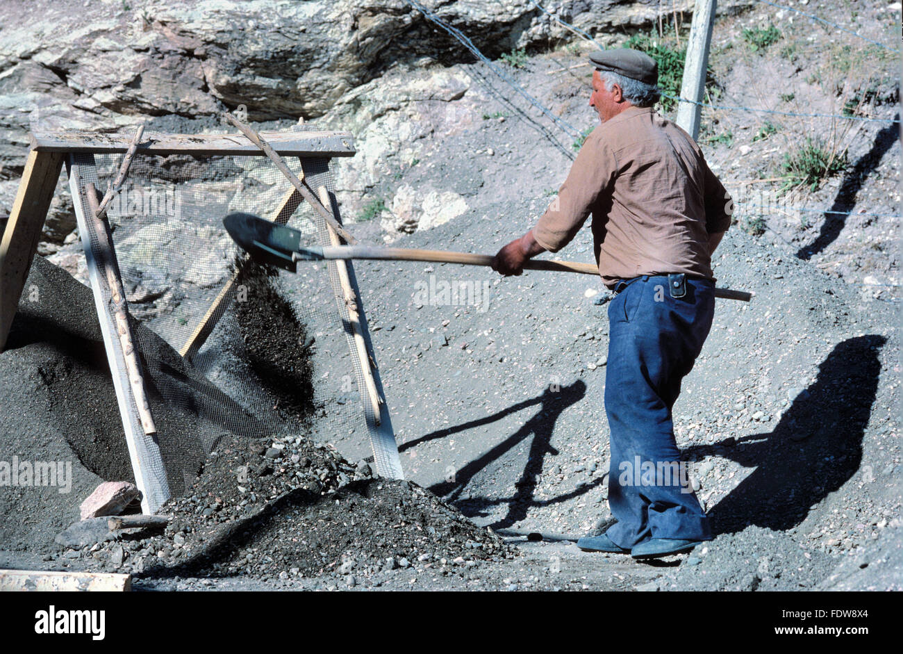 Turkish Manual Worker Workman or Construction Worker Sifting Gravel to Mix Concrete - Stock Image