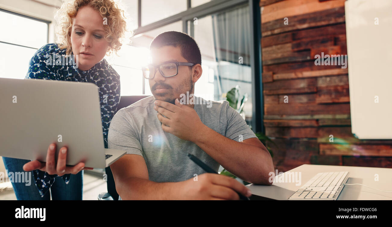 Portrait of young team of graphic designers working together in a new project, with woman showing something important Stock Photo
