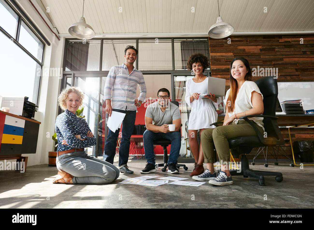 Portrait of happy young people in a meeting looking at camera and smiling. Young designers working together on a - Stock Image