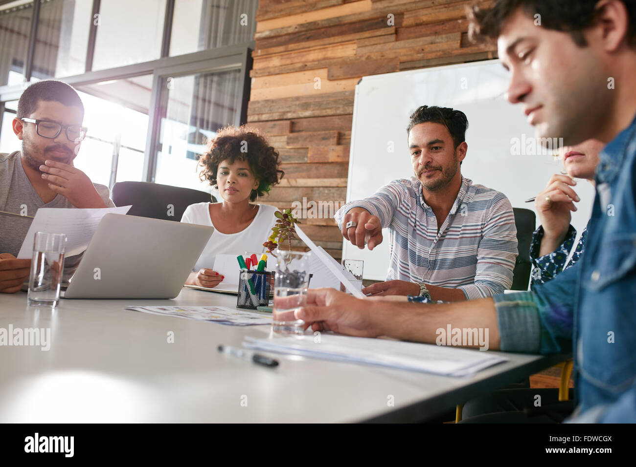 Multiracial group of business people meeting in modern office. Team holding business plan discussing about progress - Stock Image