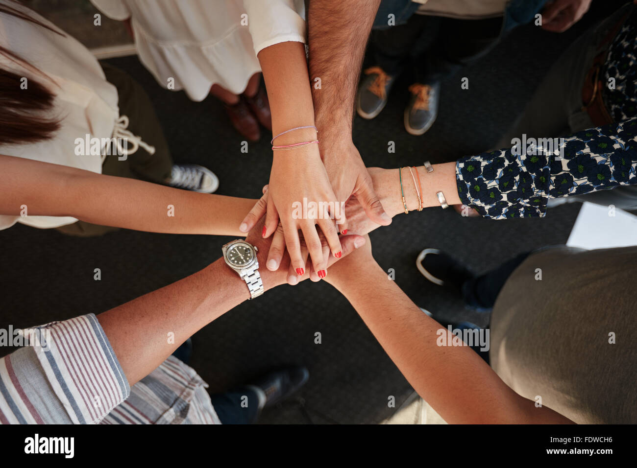 Top view of young creative professionals putting their hands together as a symbol of teamwork, cooperation and unity. - Stock Image