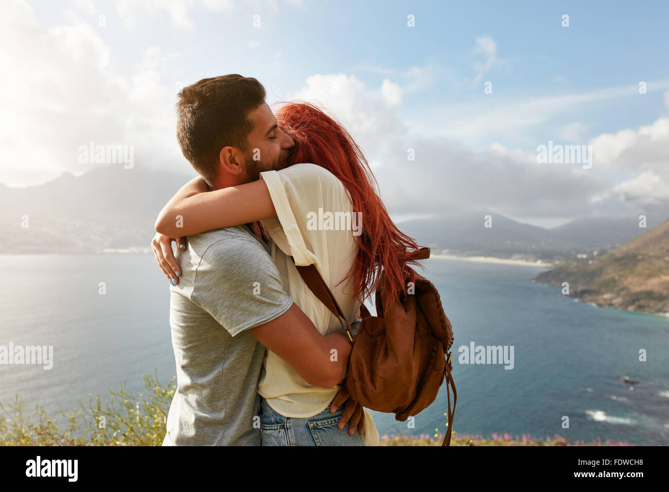 Portrait of a happy young couple enjoying a romantic embrace outdoors. Young man hugging his girlfriend while standing - Stock Image