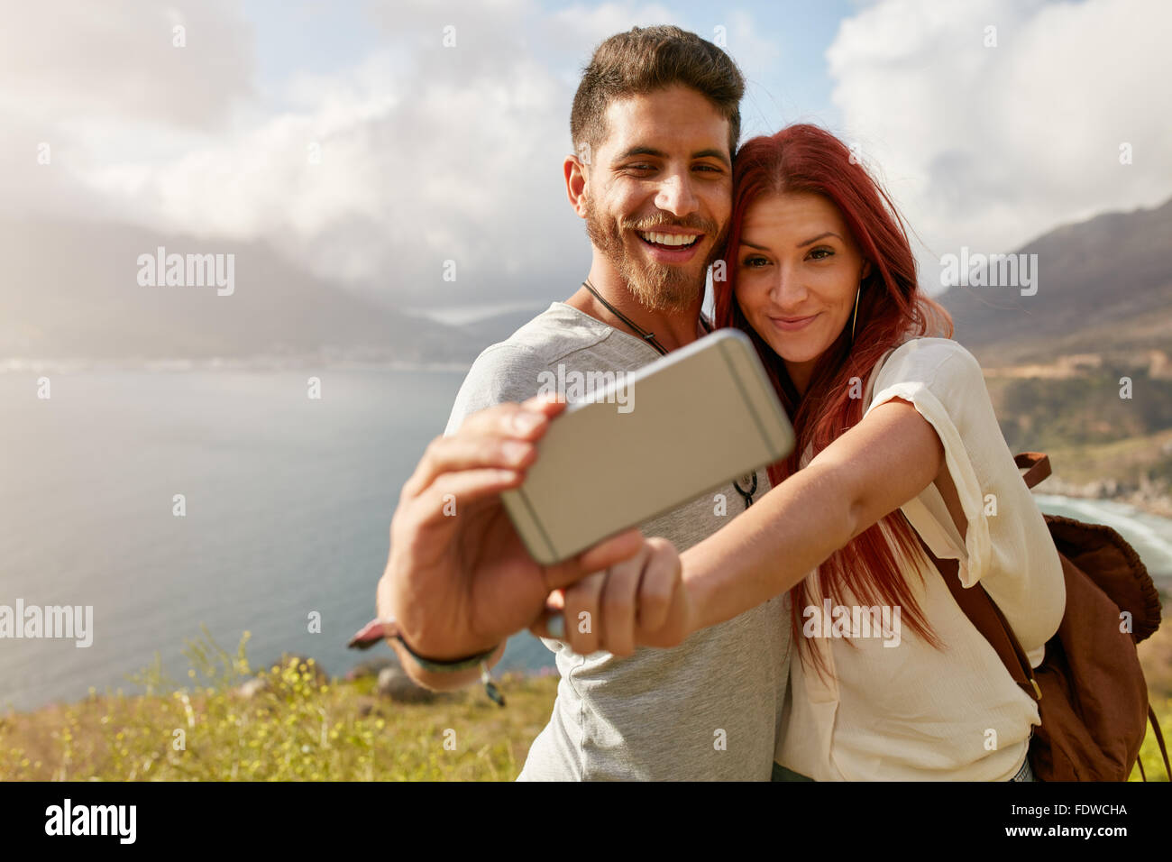 Young couple hiking taking selfie with smart phone. Happy young man and woman taking self portrait with mountain - Stock Image