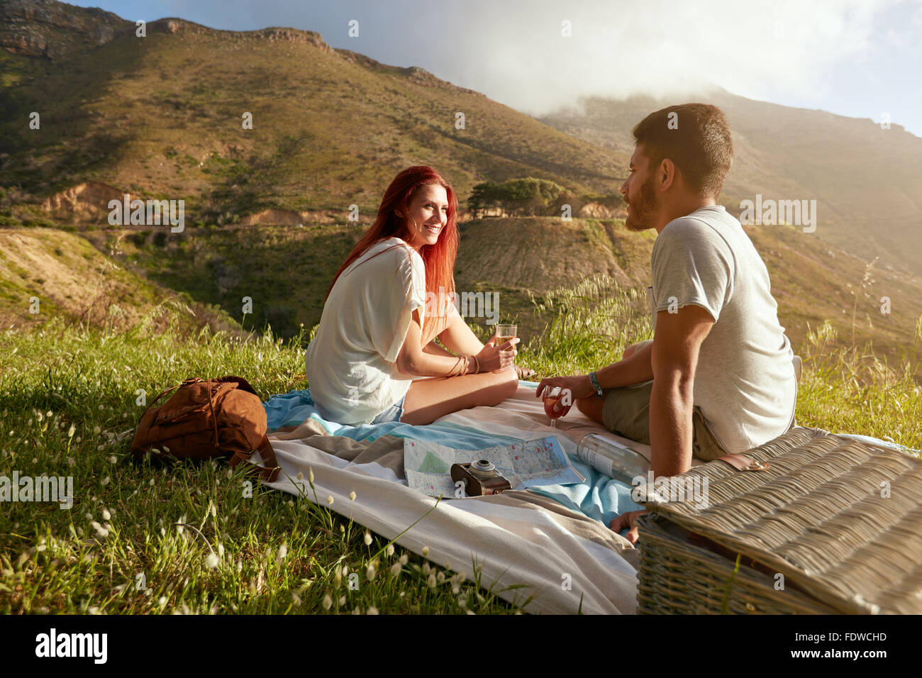 Young man and woman sitting on the grass during a picnic with glass of wine. Loving young couple having a conversation - Stock Image