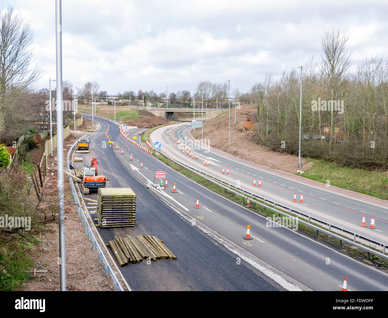 Construction of a new road layout with a digger and coned off area of dual carriageway. - Stock Image