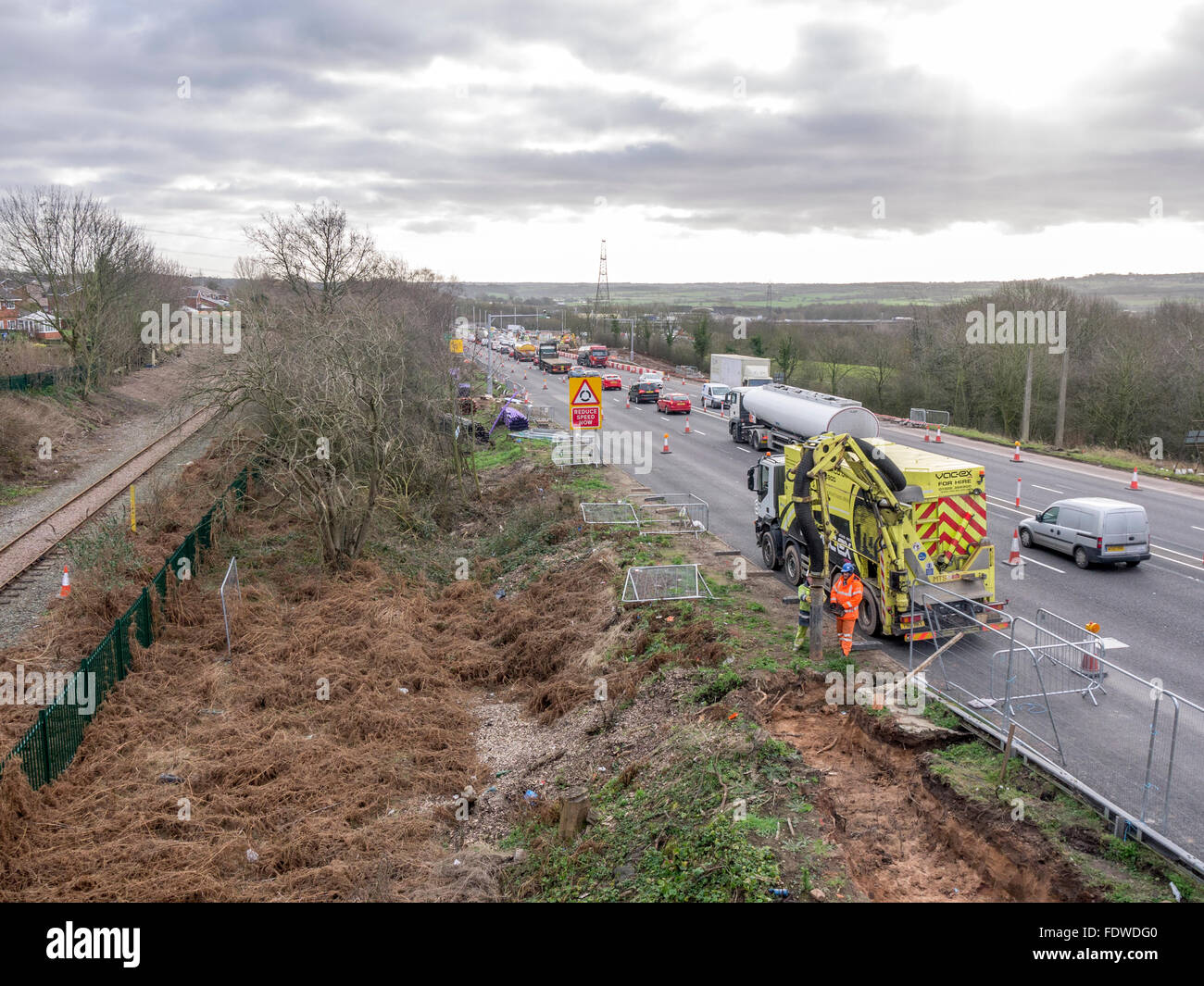 Workers on side of a coned off dual carriageway doing maintenance work. - Stock Image