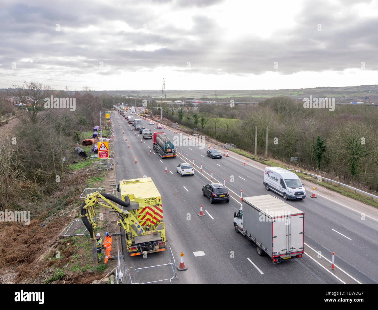 Workers on side of a coned off dual carriageway doing some vacuum excavation. - Stock Image