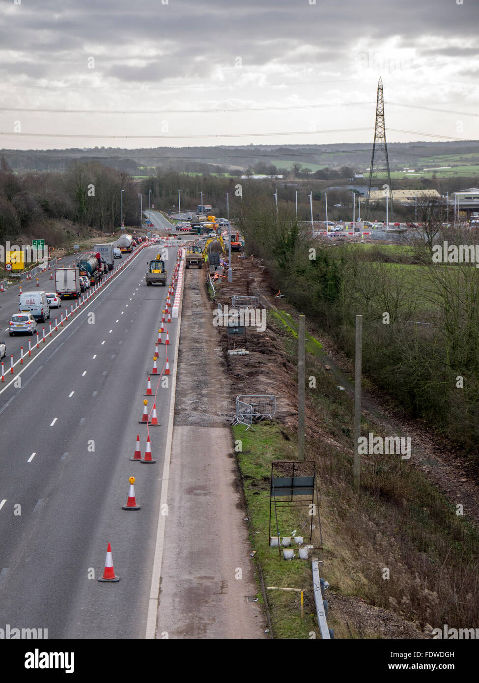 Construction on hard shoulder of road, coned off to traffic. - Stock Image