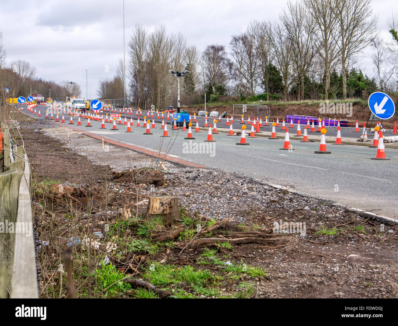 Coned off area of a road with construction vans in the distance - Stock Image