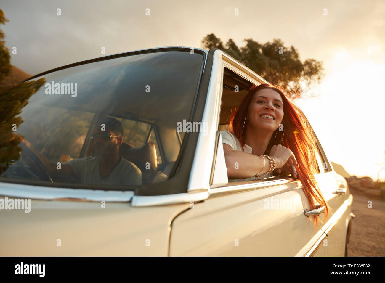 Portrait of happy young woman going on a road trip leaning out of window. Female enjoying travelling in a car with - Stock Image
