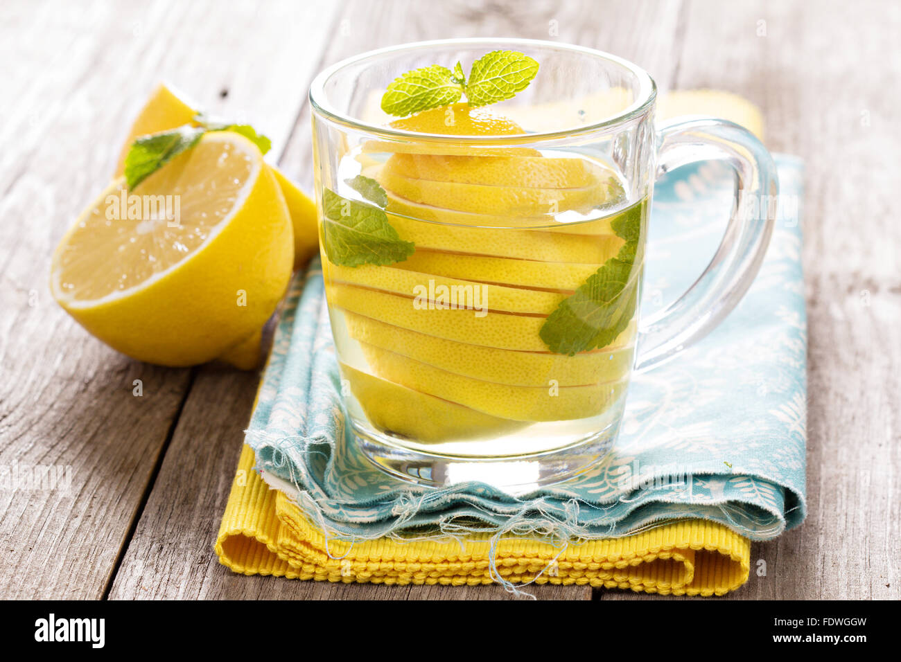 Tea with mint and whole lemon in a transparent cup. Natural medicine concept. - Stock Image