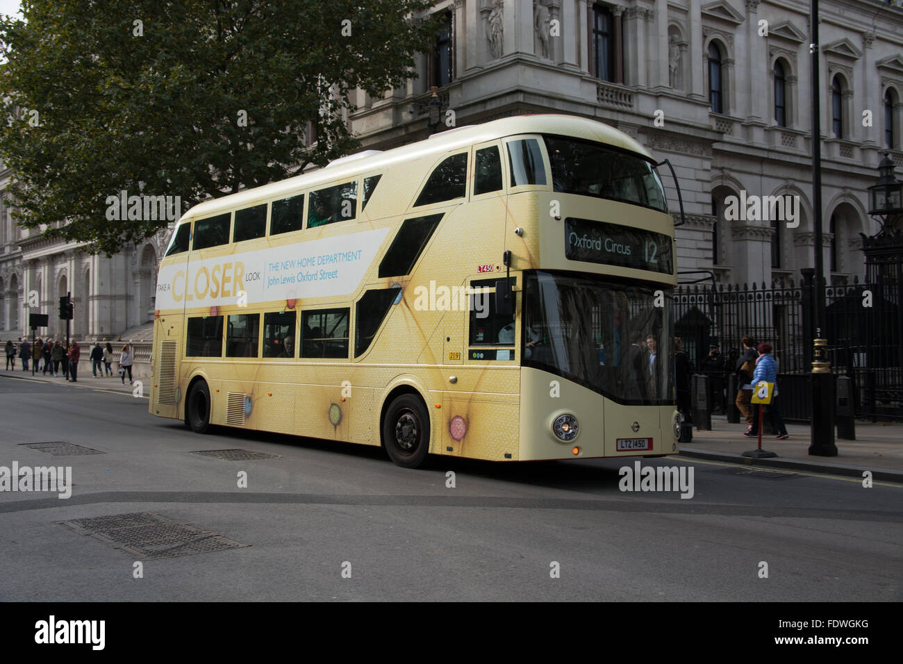 A new London Routemaster bus is coverd in an advert for the new John Lewis store home department. It is on Route Stock Photo