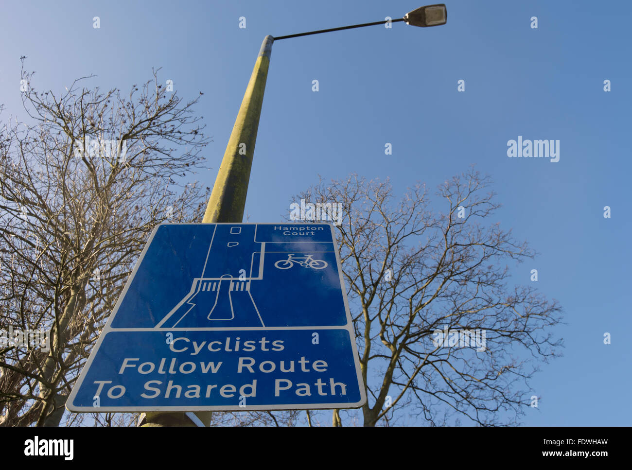 cyclists follow route to shared path sign, kingston upon thames, surrey, england - Stock Image