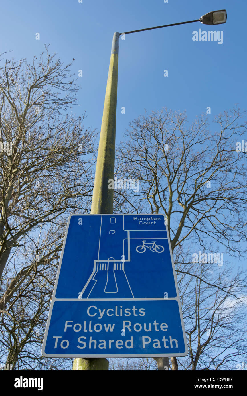 cyclists follow route to shared path sign, kingston upon thames, surrey, england Stock Photo