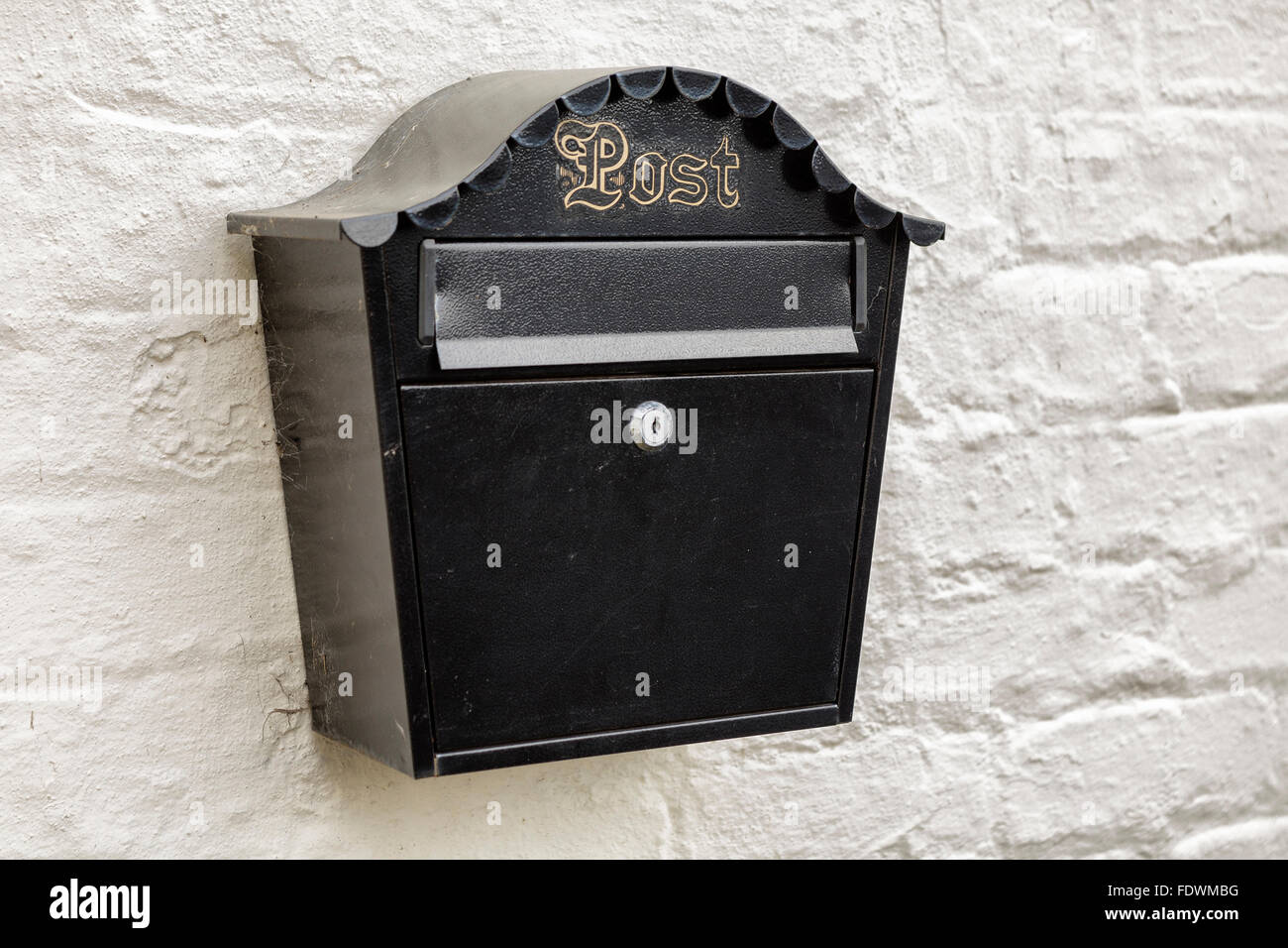 Black mailbox with gold lettering on a white brick wall  Model Release: No.  Property Release: No. - Stock Image