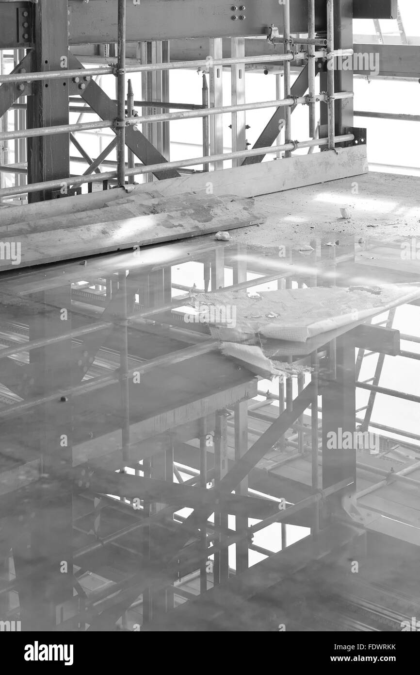 A construction site with concrete slab with water puddle and scaffolding - Stock Image
