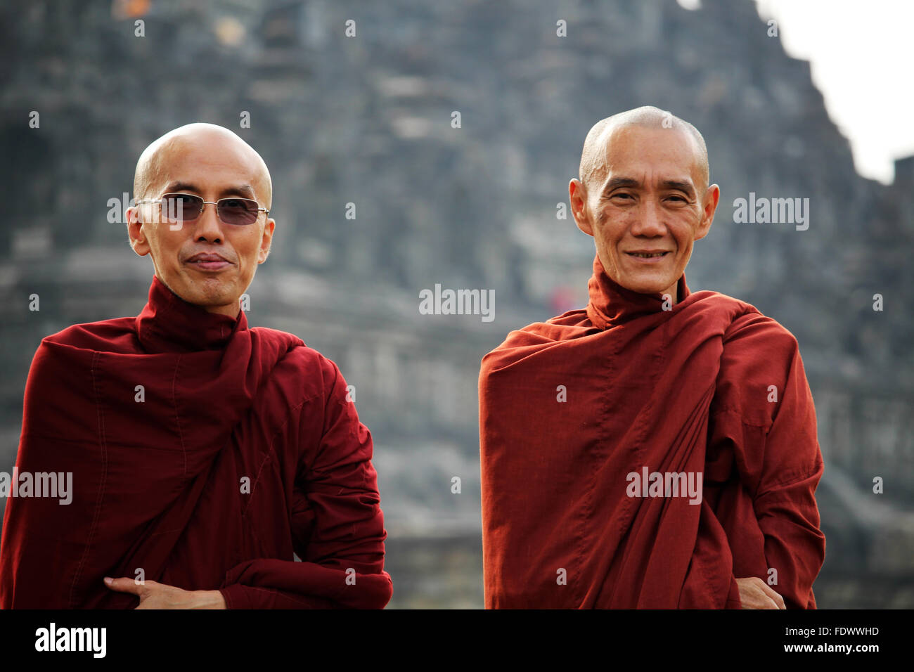 Portrait of two buddhist monks posing in front of  Borobudur Buddhist temple complex in Central Java, Indonesia - Stock Image