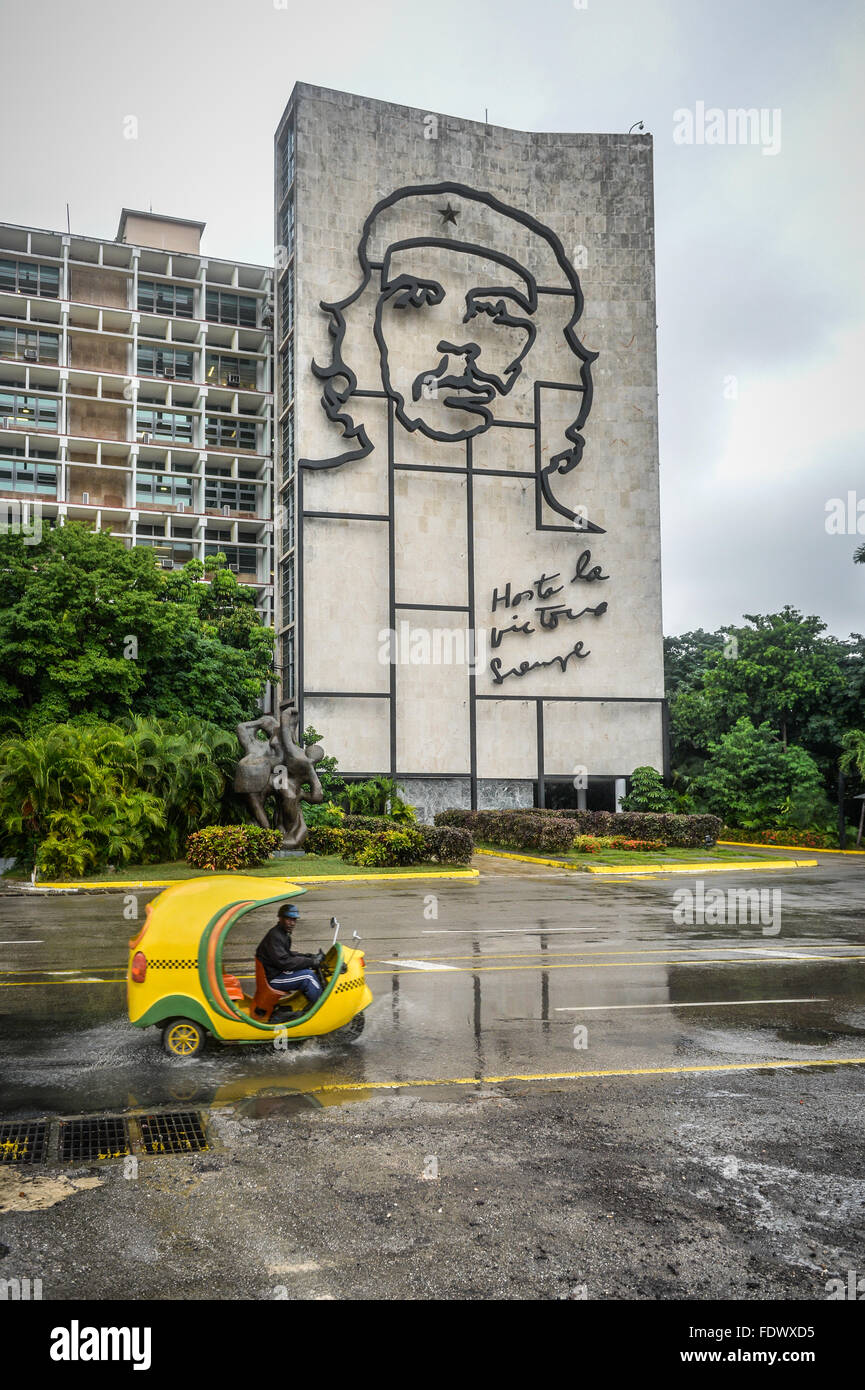 Revolution Square in Havana, Cuba on a wet day with a tourist yellow Coco Taxi looking for trade. - Stock Image