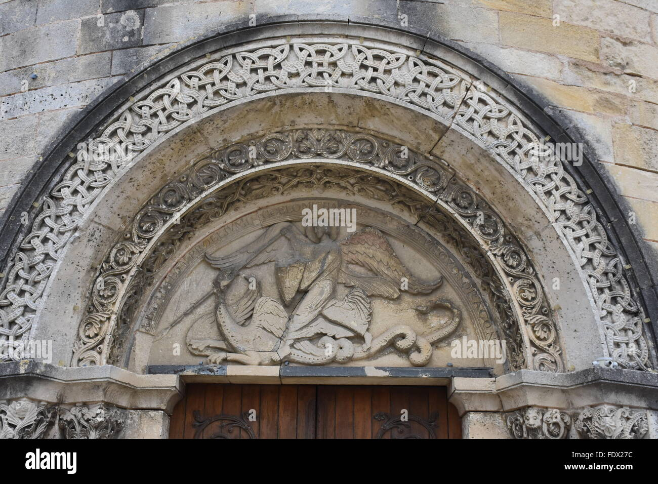Tympanum of the Eglise de Saint-Michel in the outskirts of Angouleme France, showing the archangel St Michael slaying - Stock Image
