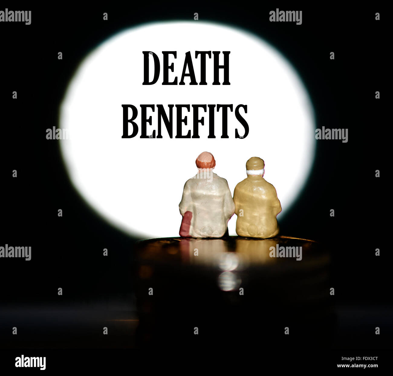 Miniature figurine pensioners sitting on coins in front of a spotlight showing the word death benefits concept - Stock Image