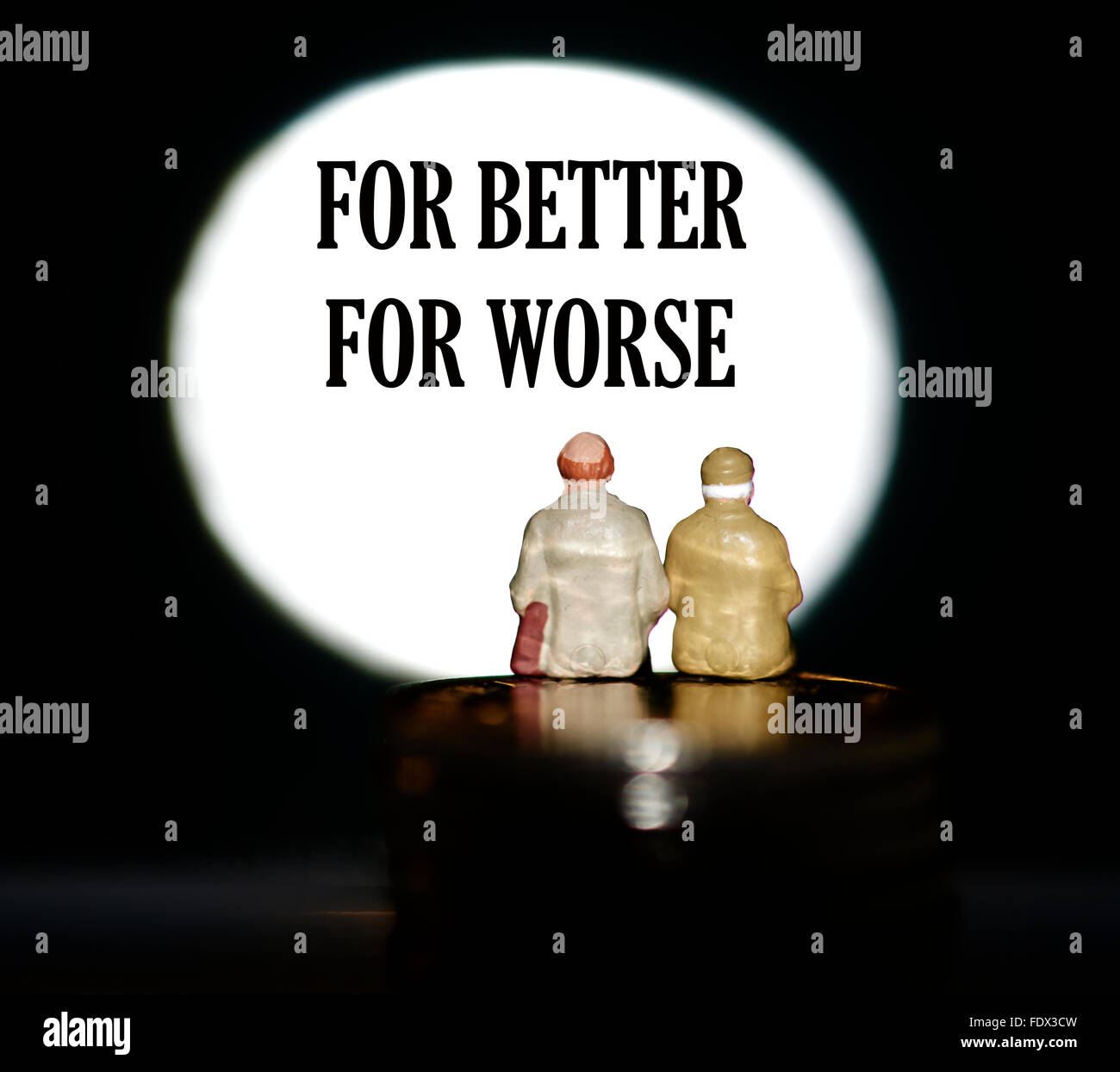 Miniature figurine pensioners sitting on coins in front of a spotlight showing the word for better for worse concept Stock Photo