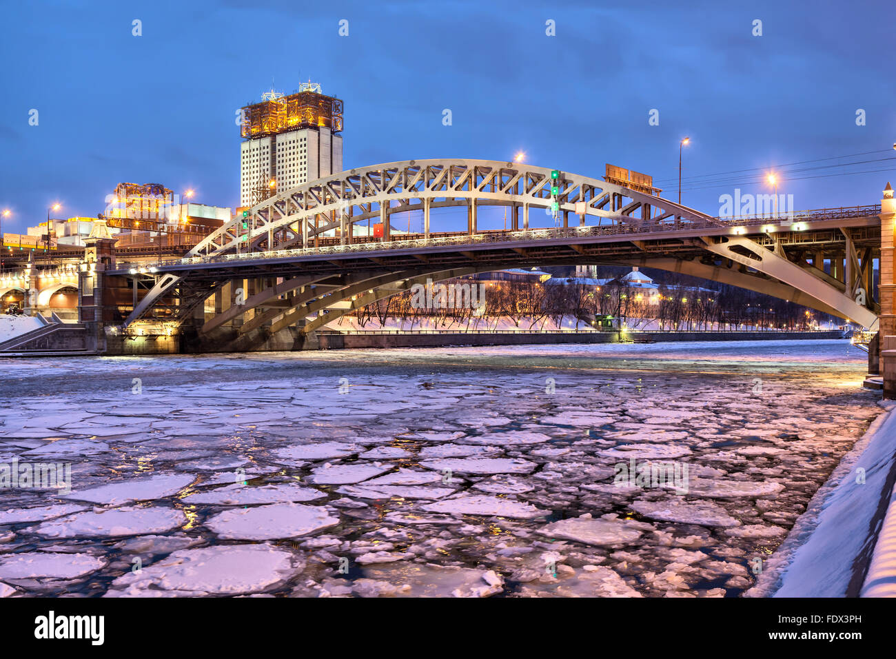 Andreevsky railroad bridge across Moscow river and building of Science Academy in the evening, Moscow, Russia - Stock Image