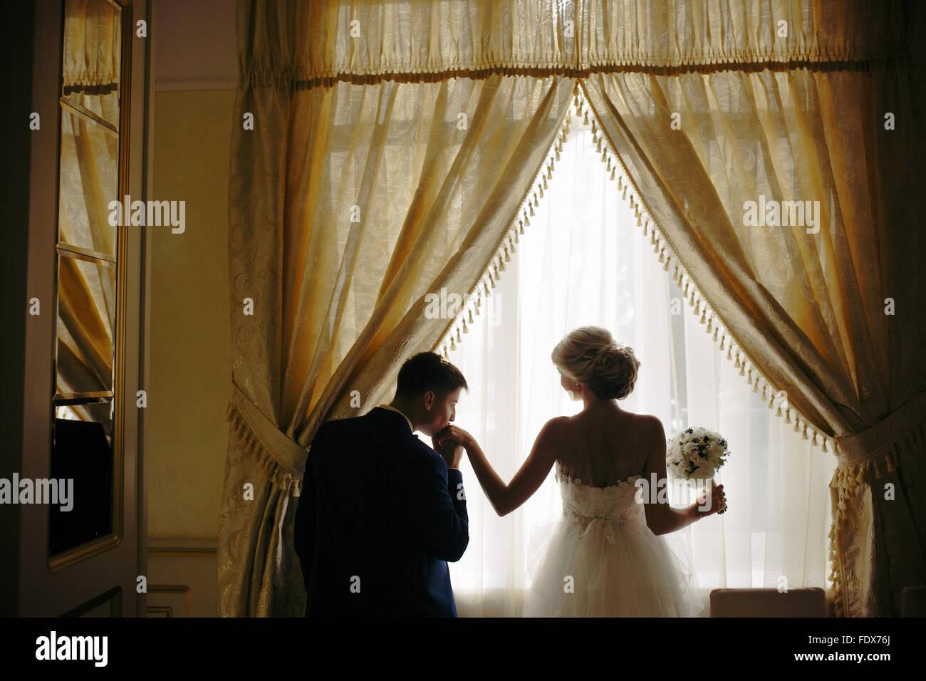 bride and groom standing in front of window - Stock Image