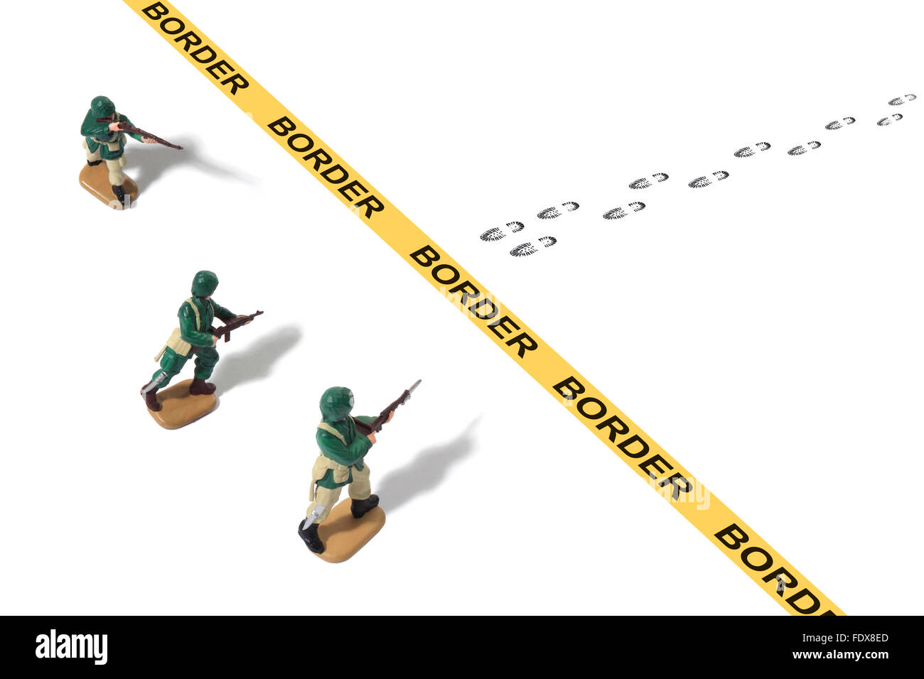 Studio shot of toy Army men protecting border from threat - Stock Image