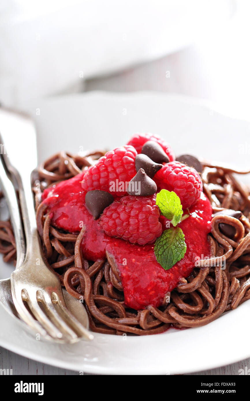 Cooked chocolate pasta spaghetti with raspberry sauce - Stock Image