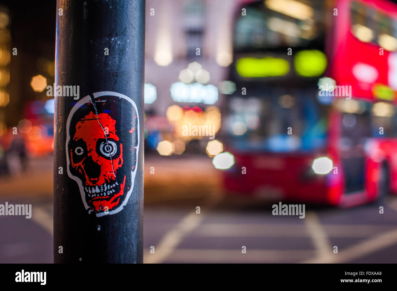 Eerie skull sticker on pole at night in Central London - Stock Image