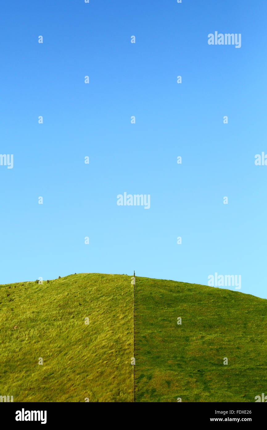 A fence bisecting a grassy hill under a clear blue sky - it appears that the grass may indeed be greener on the Stock Photo