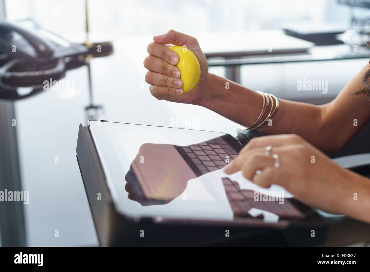 Office worker typing email on tablet computer. The woman feels stressed and nervous, holds an antistress yellow - Stock Image