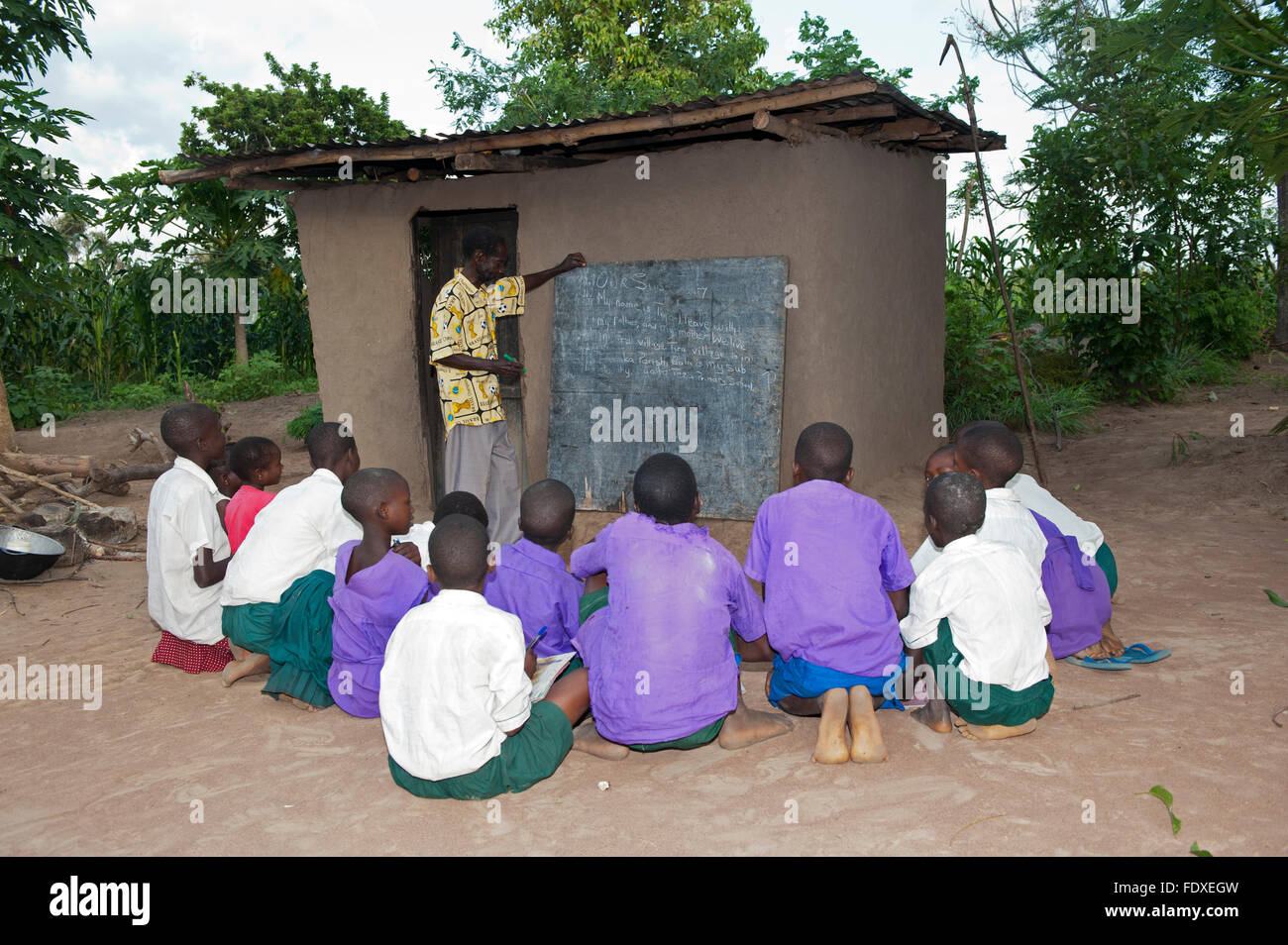 Children learning from a teacher at an outside classroom, Uganda. - Stock Image