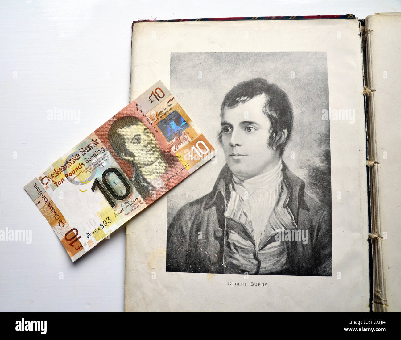 Ten pound note with portrait of Robert Burns lying on top of a portrait of him illustrated in an old book. - Stock Image