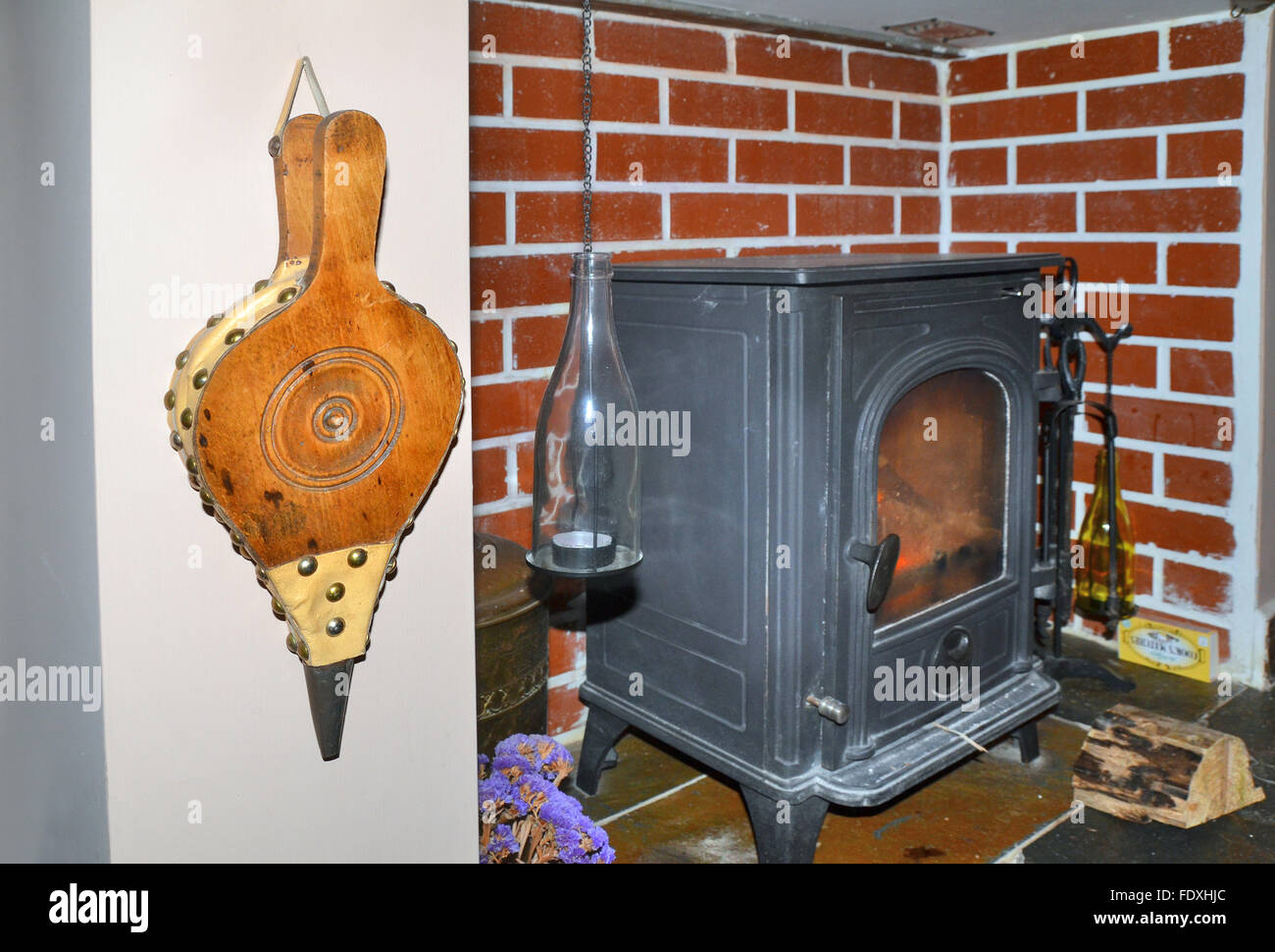 Wooden Fire Bellows Hanging Close To An Indoor Wood Burning Stove