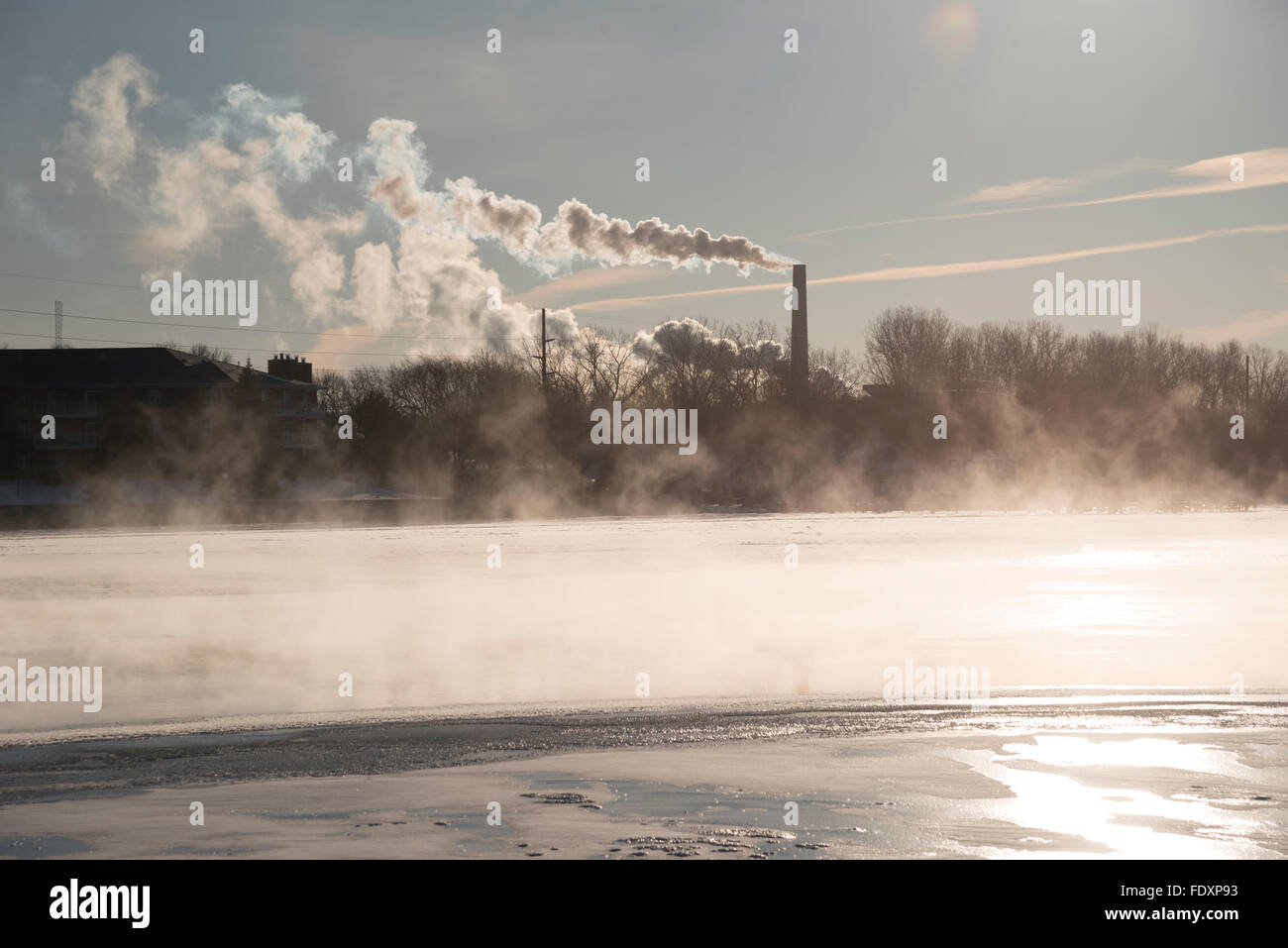 Steam rises off the water of the river and smoke and pollution puff out of a large coal smokestack on a cold winter - Stock Image