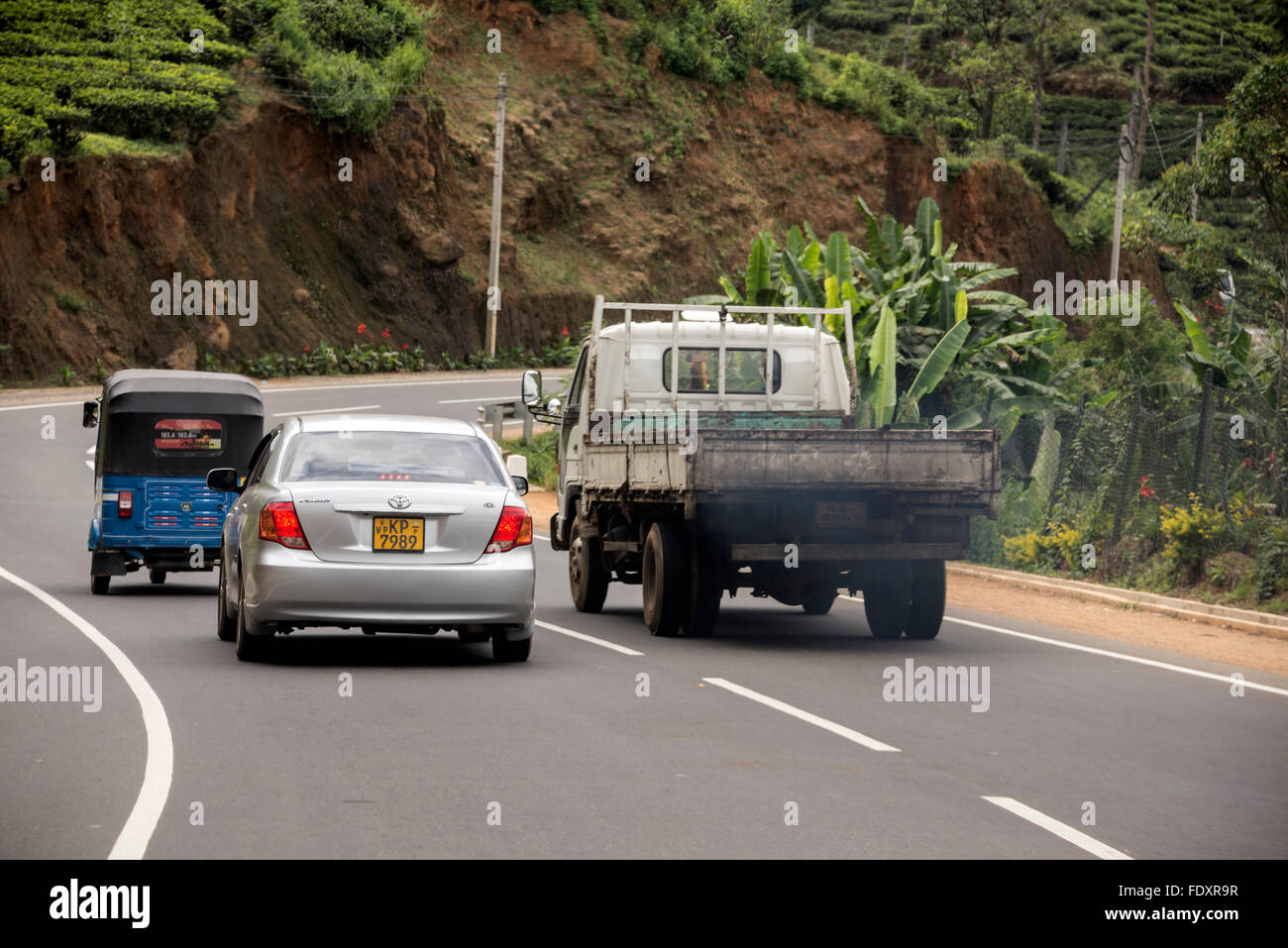 A pickup truck belching out polluted exhaust of diesel fumes as it overtakes other vehicles whilst approaching  Stock Photo