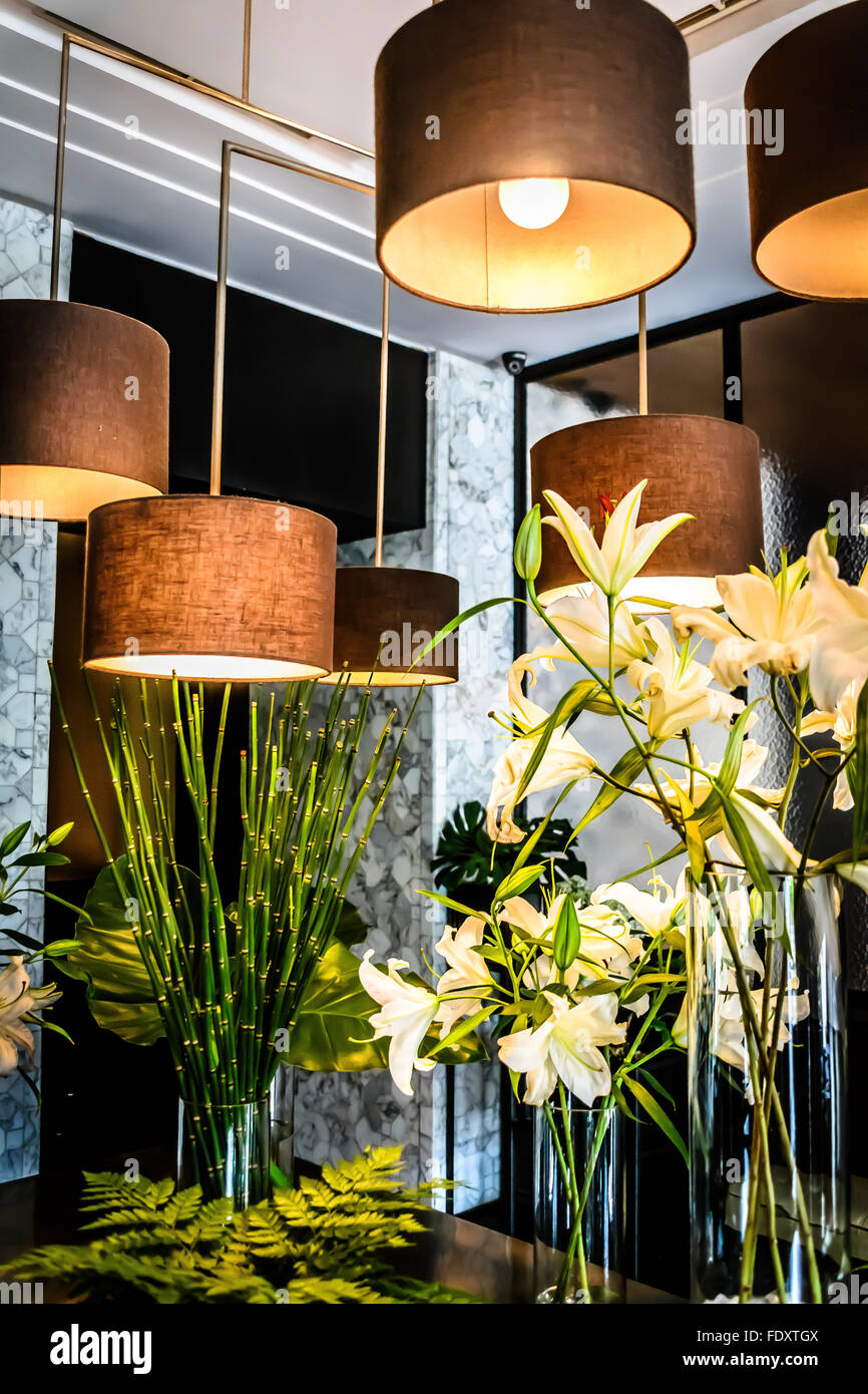 Hanging lights and lilies flower arrangements Stock Photo