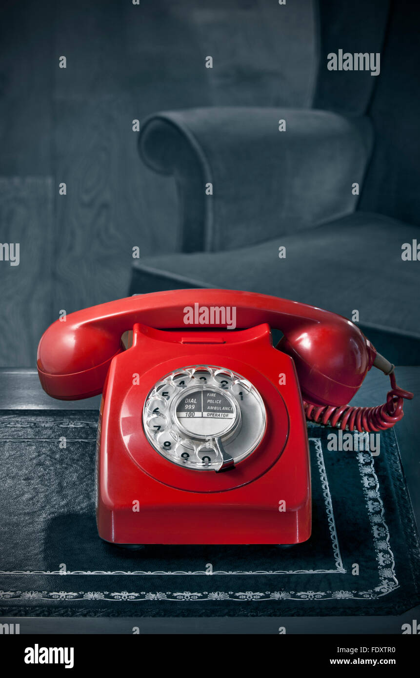 1960's red old retro dial telephone laquer 60's/70's GPO red BT phone on antique desk with atmospheric B&W - Stock Image