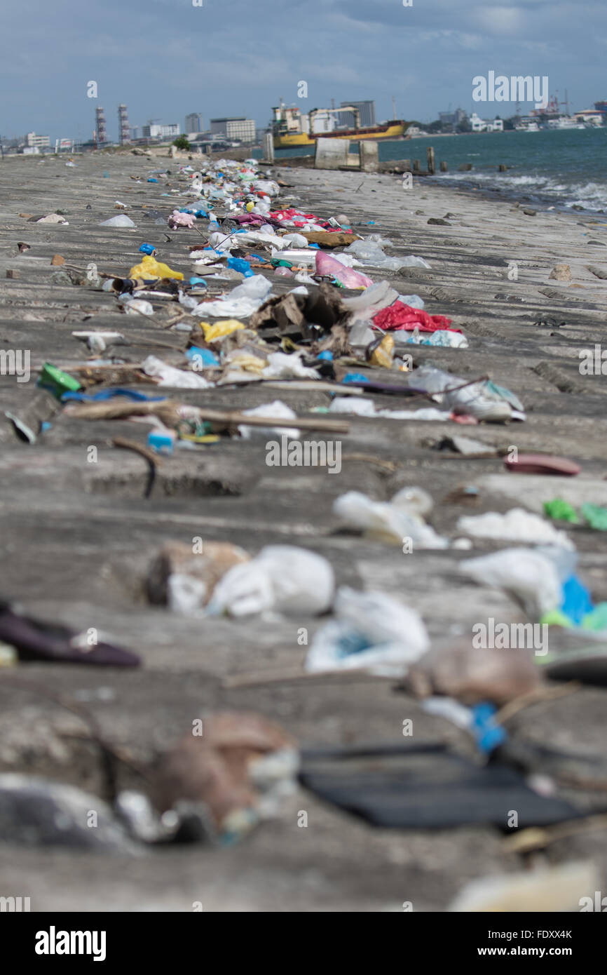 The tide recedes leaving a thick line of mainly plastic garbage along the shipping channel banks leading to the - Stock Image