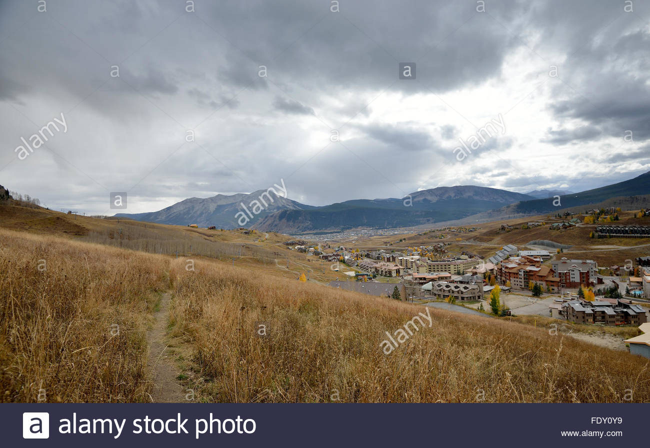 A narrow hiking trail winds through the grass overlooking Mt. Crested Butte, Colorado on an overcast autumn day Stock Photo