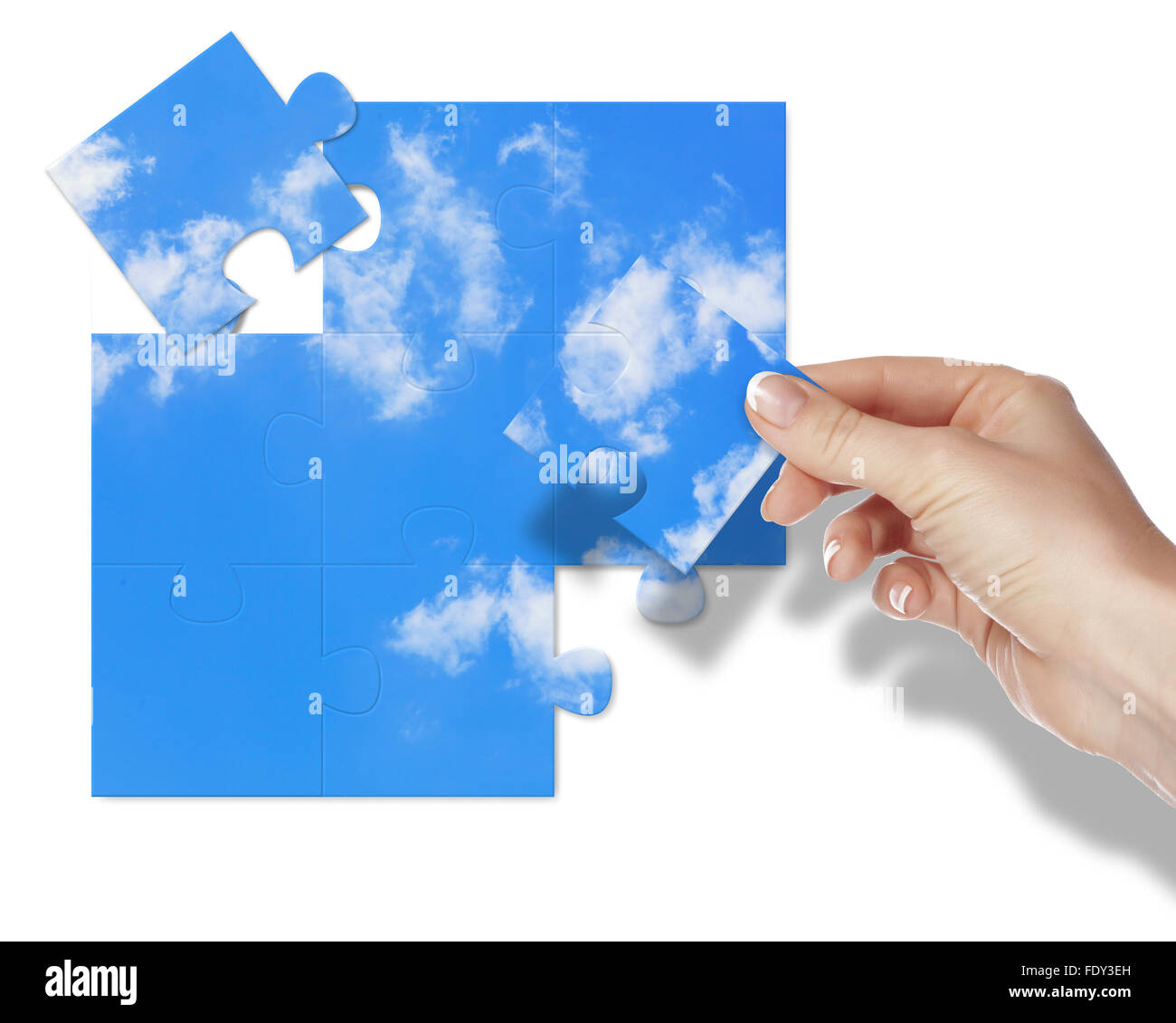 Image of a puzzle with blue sky and white clouds - Stock Image