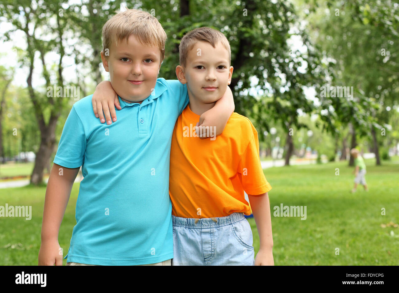 two boys standing next to each other in the summer park stock photo