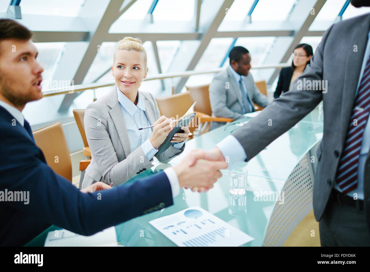 Happy businesswoman looking at one of businessman handshaking with partner - Stock Image