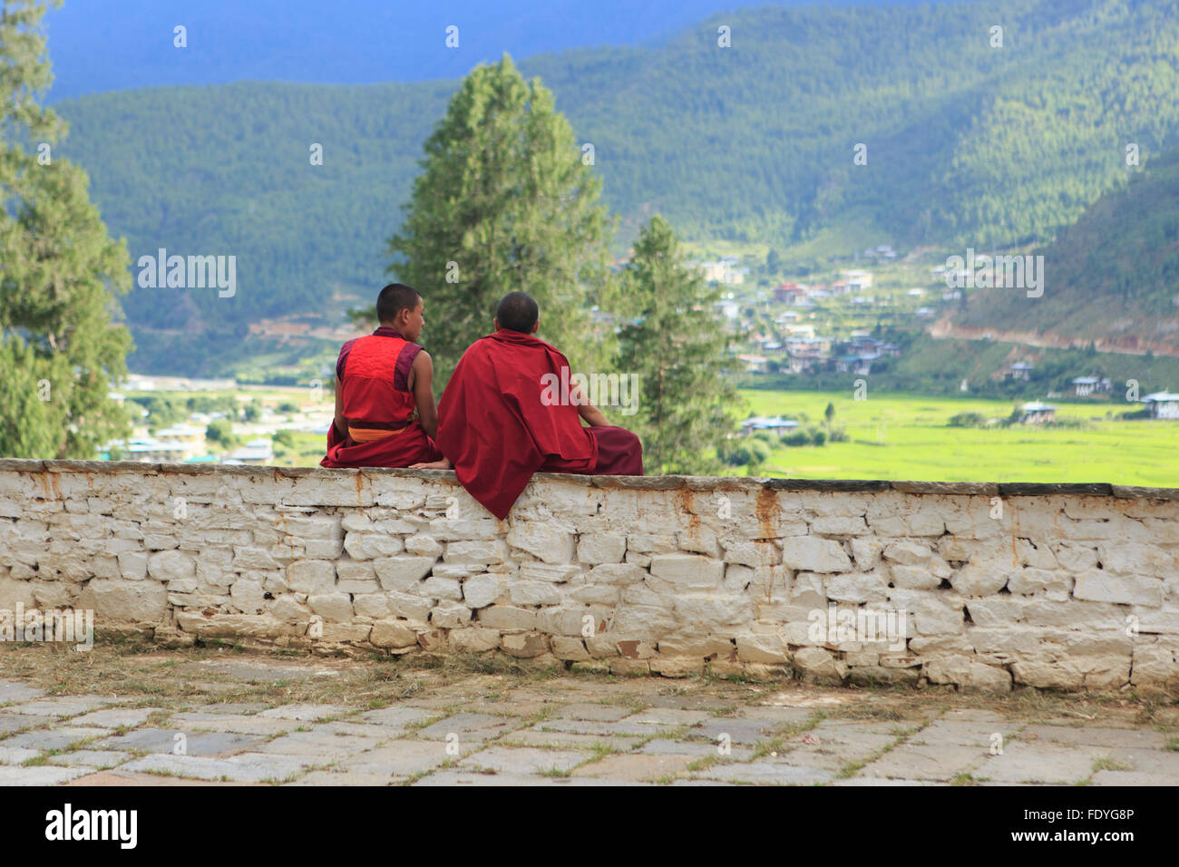 Two monks sit on a wall in Thimphu, Bhutan Stock Photo