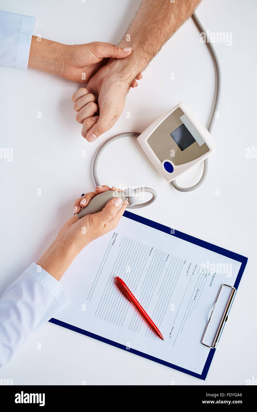 Hands of doctor measuring blood pressure of patient - Stock Image