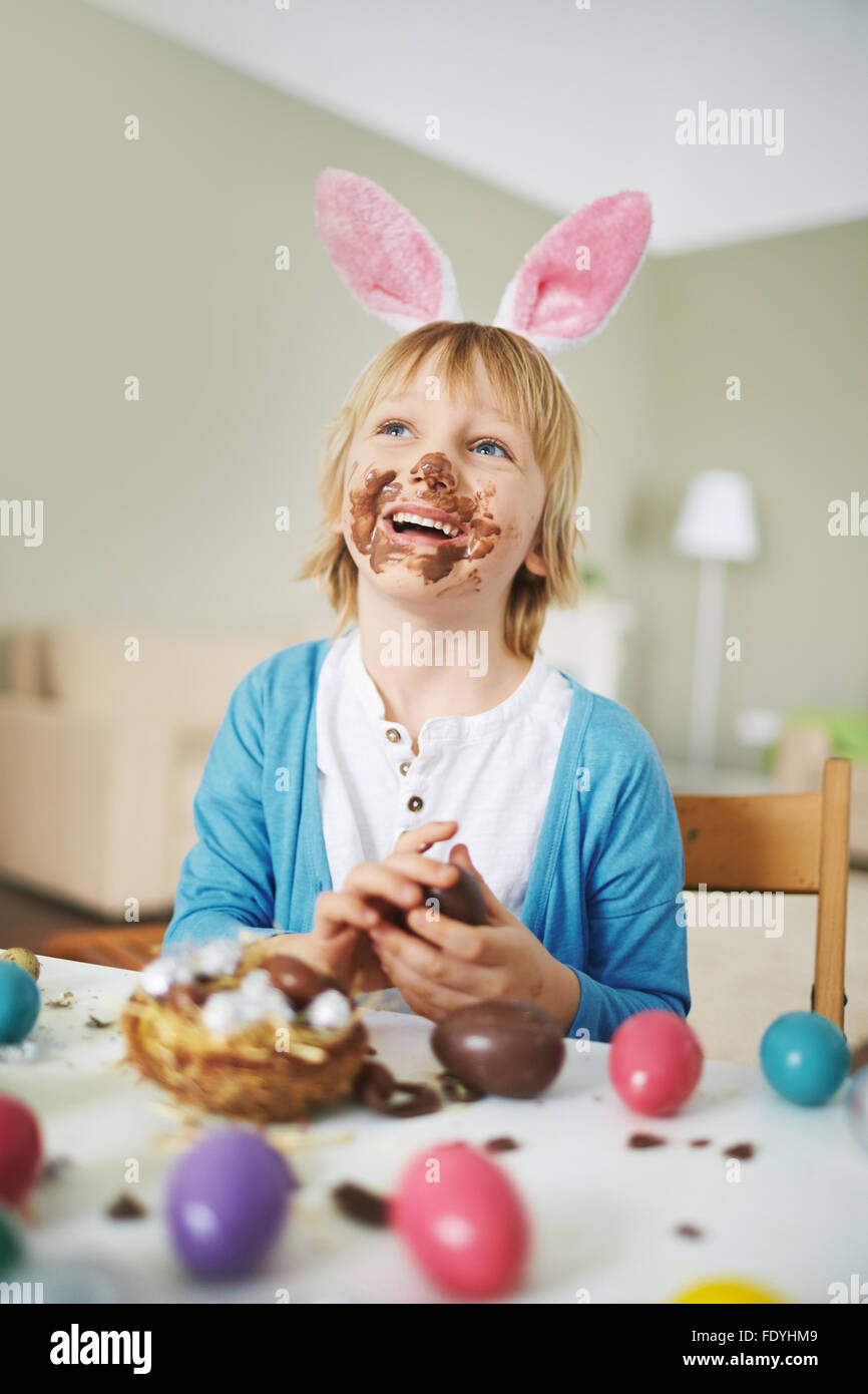 Happy boy with rabbit ears eating chocolate eggs by Easter table - Stock Image